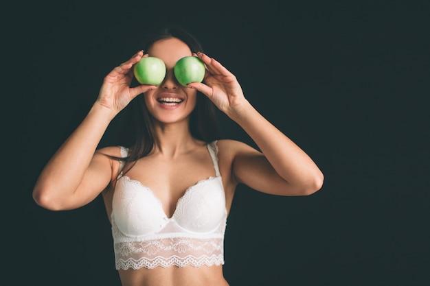 여성 모델 녹색 신선한 사과 닫습니다. 다이어트에 채식 소녀입니다. 젊은 여자는 긴 검은 머리를 격리했습니다. 그 소녀는 스포츠 인물이 있으며 흰 속옷을 입었습니다.