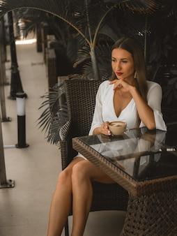 Женская модель пьет кофе в ресторане. фото бежевого цвета