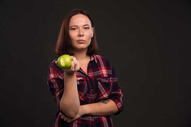 Modello femminile in abiti collezione autunno inverno che tiene una mela verde, vista frontale.
