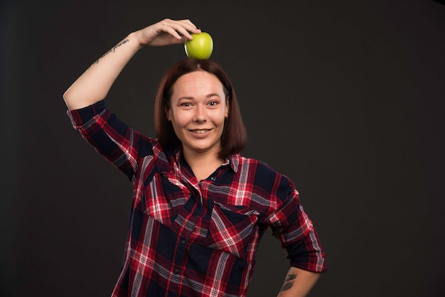 Female model in fall winter collection outfits holding a green apple on the head .
