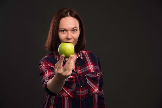 Modello femminile in abiti da collezione autunno inverno che tiene una mela verde e guarda con appetito.