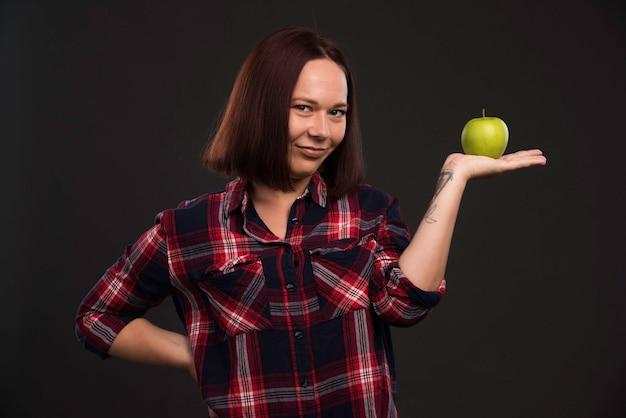 Modello femminile in abiti da collezione autunno inverno tenendo una mela verde e indicandola.