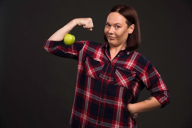 Modello femminile in abiti della collezione autunno inverno che tiene una mela verde e se la mette sui muscoli.