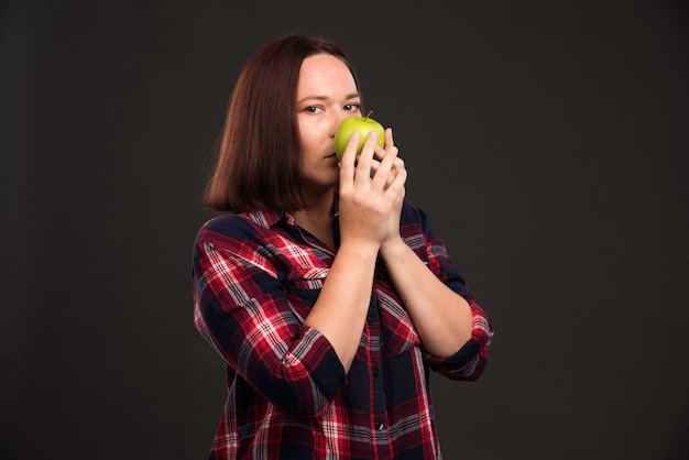 Female model in fall winter collection outfits holding a green apple and smelling it.
