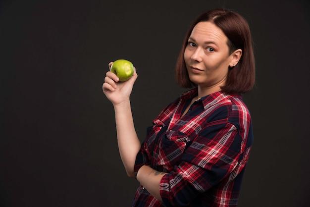 Modello femminile in abiti collezione autunno inverno in possesso di una mela verde.