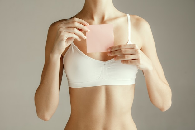 Female model holding empty pink sticky note