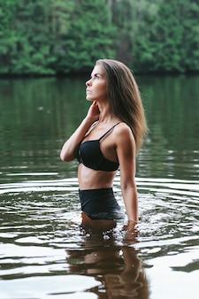 湖の黒い水着の女性モデル