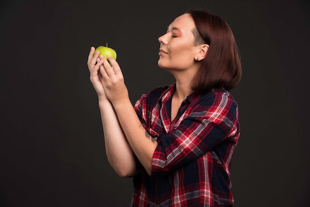 가을 겨울 컬렉션 의상 여성 모델은 녹색 사과를 들고 그것을 즐기고 있습니다.