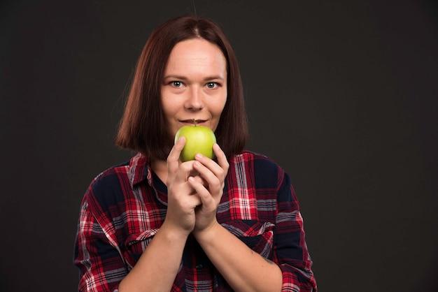Женская модель в осенне-зимней коллекции нарядов держит зеленое яблоко и чувствует себя взволнованным.