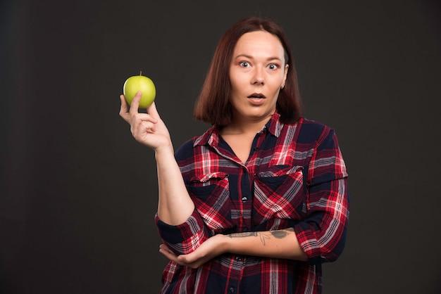 Девушка-модель в нарядах из коллекции осень-зима держит зеленое яблоко и чувствует себя удивленной.