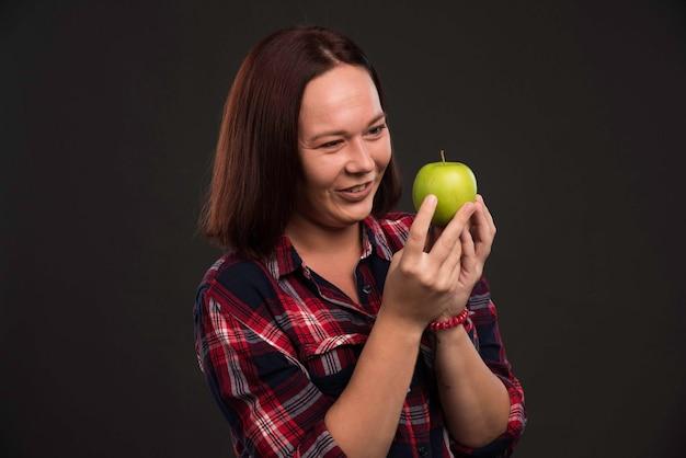 가을 겨울 컬렉션 의상 여성 모델은 녹색 사과를 들고 식욕을 찾고 있습니다.