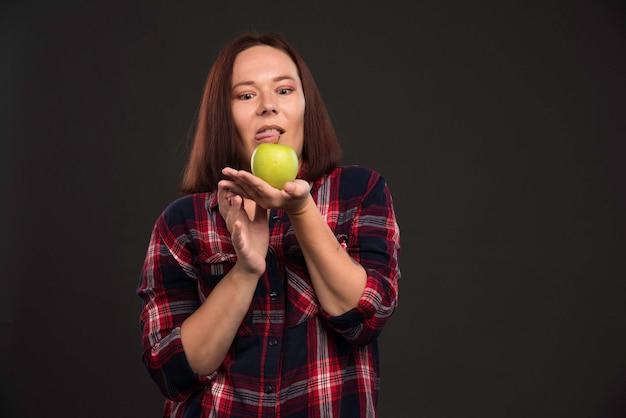 가을 겨울 컬렉션 의상 여성 모델은 녹색 사과를 들고 겁에 질린 것 같습니다.