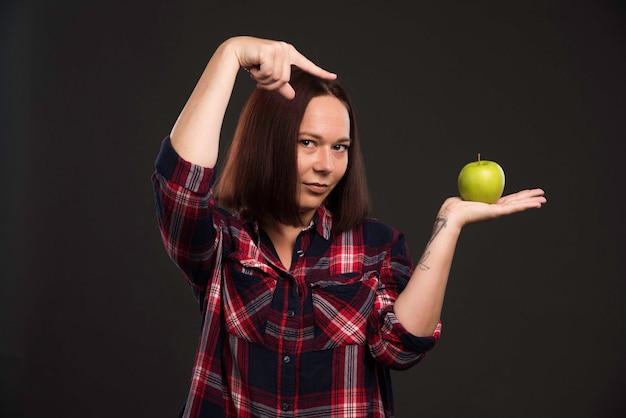 Женская модель в нарядах коллекции осень-зима держит зеленое яблоко и указывает на него.
