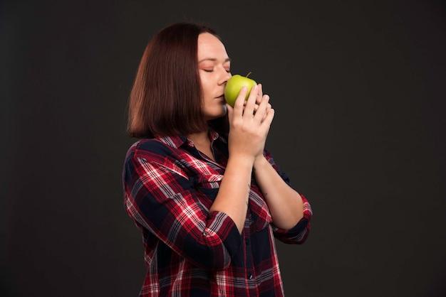 Девушка-модель в нарядах осенне-зимней коллекции держит зеленое яблоко и нюхает его.