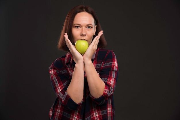 그녀의 입에 녹색 사과 들고 가을 겨울 컬렉션 의상 여성 모델.