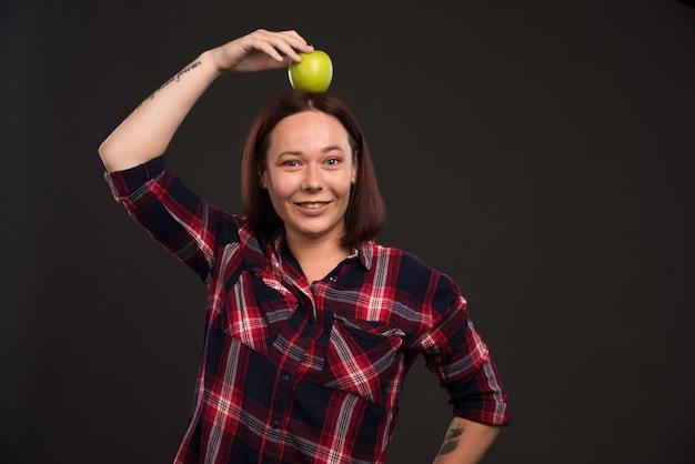 Девушка-модель в осенне-зимних нарядах держит зеленое яблоко на голове.