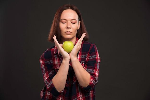 Девушка-модель в нарядах из осенне-зимней коллекции держит зеленое яблоко под подбородком.