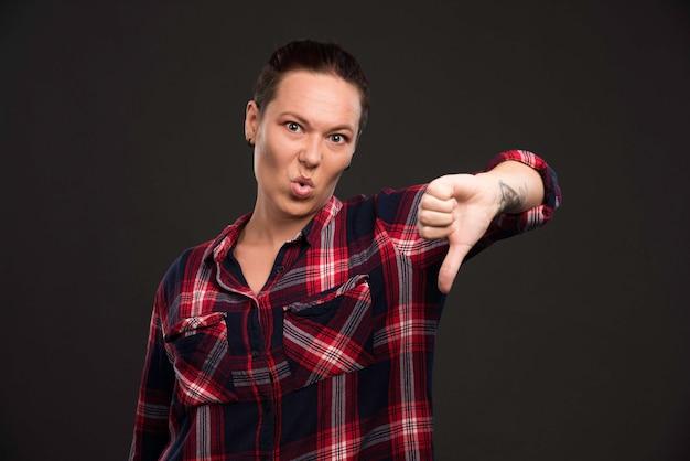 親指を下に向ける秋冬コレクションの衣装の女性モデル。