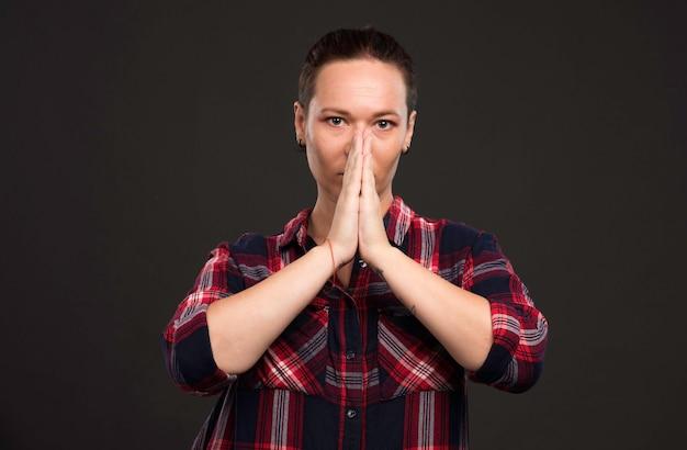 Женская модель в осенне-зимних нарядах молится.