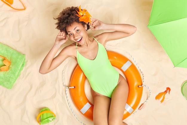 膨らんだ救命浮輪の緑のビキニのポーズの女性モデルは頭の後ろに手を保ちます夏休みを楽しんでいます日焼け止めローションは完璧な休日の間に幸せな気分を持っています
