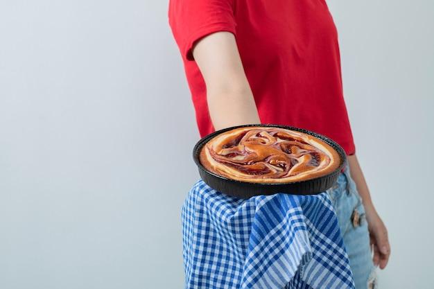 Женская модель в красной рубашке держит сладкий пирог в черной сковороде.