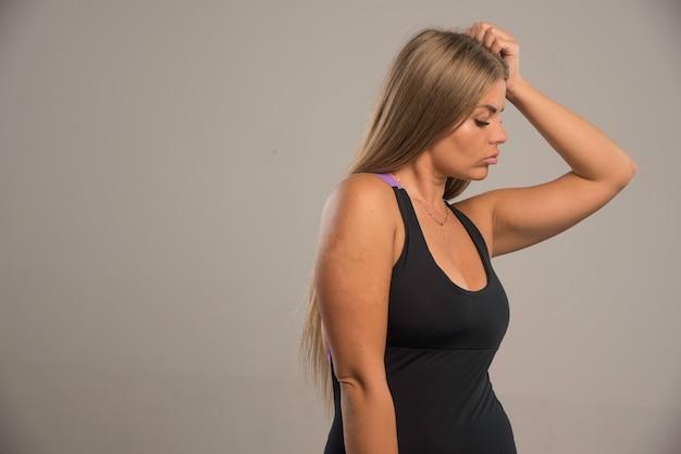 У девушки-модели в спортивном бюстгальтере болит голова.