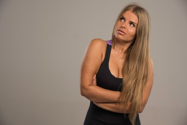 Девушка в спортивном бюстгальтере выглядит серьезно с закрытыми руками.
