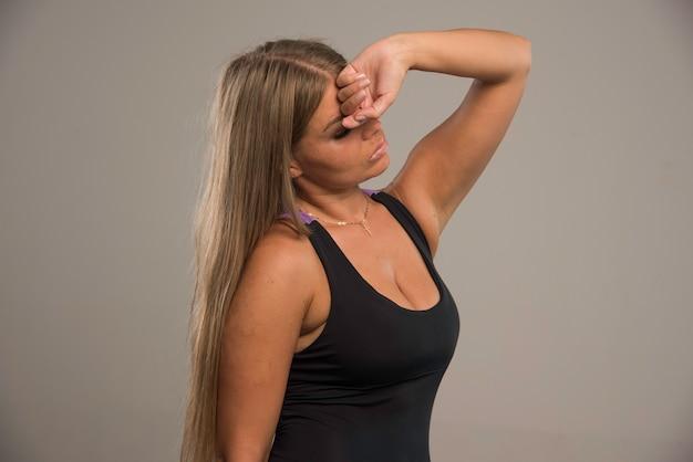 스포츠 브래지어의 여성 모델은 이마에 손을 대고 피곤해 보입니다.