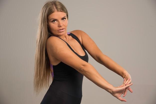 トレーニング前に腕を伸ばしてやる気に見えるスポーツブラの女性モデル。