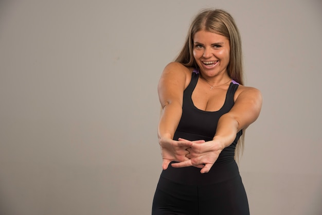 トレーニング前に腕を伸ばしているスポーツブラの女性モデルで、ポジティブに見えます。
