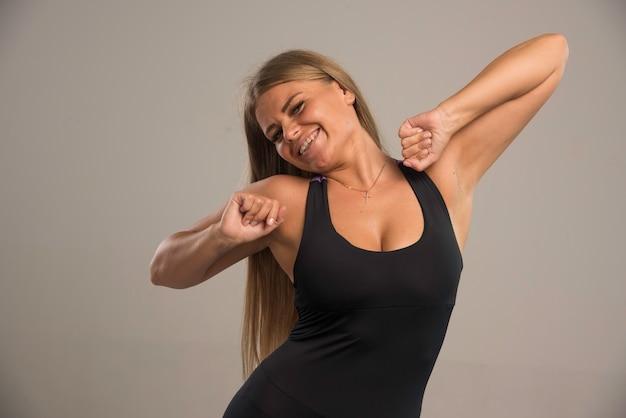 トレーニング前に背中の筋肉を伸ばすスポーツブラの女性モデル。