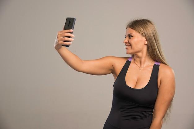 Женская модель в спортивном бюстгальтере, принимая ее селфи.