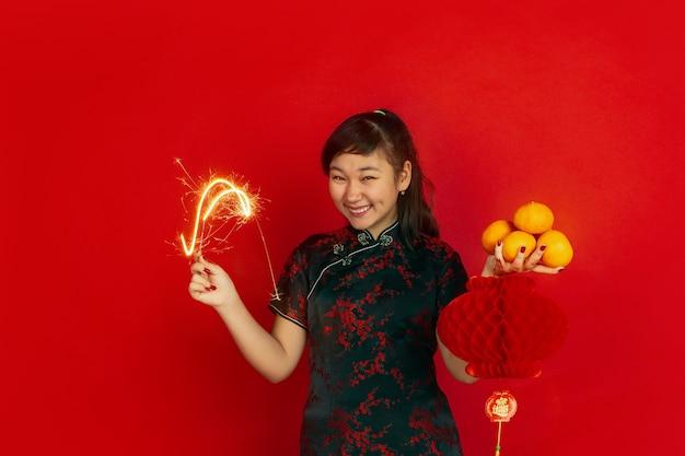 Женская модель в традиционной одежде держит мандарины, фонарь и бенгальский огонь