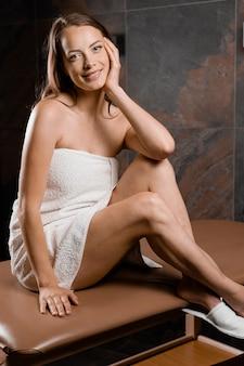 여성 모델은 스파에서 마사지 테이블에 앉아있다. 완벽 한 피부를 가진 여자의 아름다움 초상화.