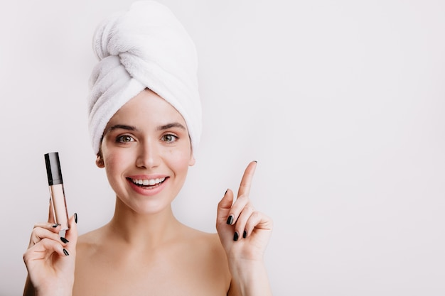 여성 모델은 얼굴의 결점을 숨기는 방법을 알고 미소로 피부 교정기를 보여줍니다.