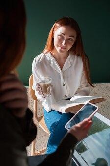 女性モデルは、一杯のコーヒーを手に彼女の友人に耳を傾けます。若い女性は一杯のコーヒーを保持し、本を読む