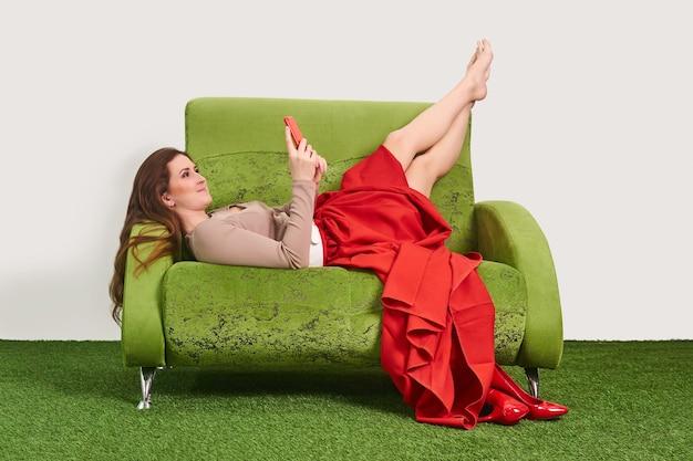 Девушка-модель смотрит в смартфон, отдыхая на диване с поднятыми вверх ногами между съемками