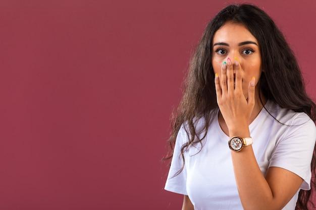 Il modello femminile fa la faccia sorpresa, vista frontale sulla parete rosa.