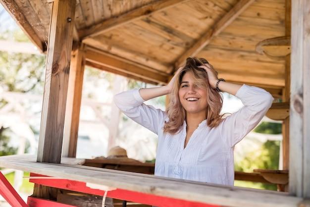 Женская модель позирует в деревянной беседке возле озера ар-сити-парк
