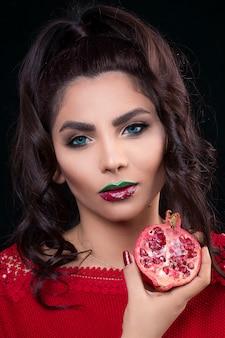 Modello femminile in rossetto rosso che tiene un melograno