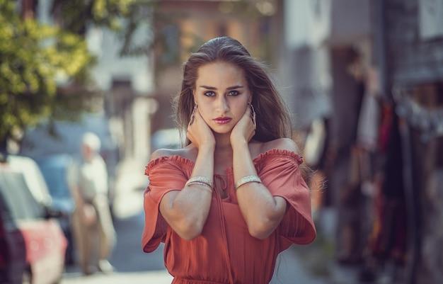 Modello femminile in un vestito rosso-arancio su una strada con una superficie sfocata