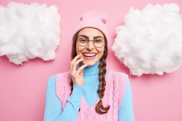 여성 모델 미소는 행복 한 감정을 광범위하게 표현하고 하얀 치아가 분홍색에 고립 된 투명 안경 라운드 캐주얼 옷을 입고있다