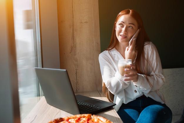 Женская модель разговаривает по телефону и держит чашку кофе. молодая женщина сидит в кафе и улыбка.