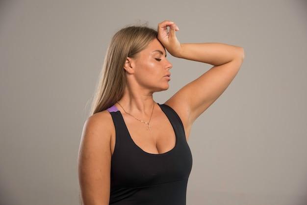 Female model in sport bra holds her head