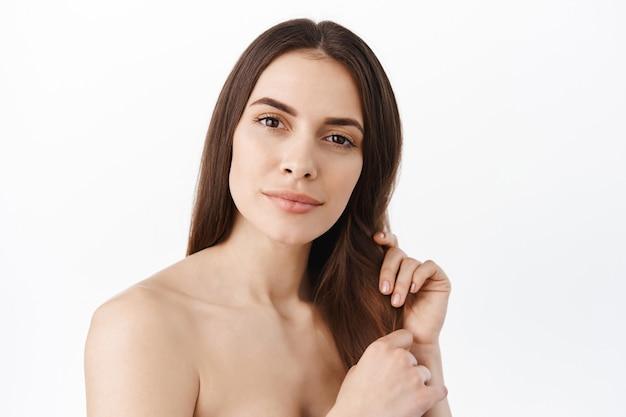 健康的な長い髪に触れる女性モデル、シャワーで裸の肩を洗う、ヌードメイク、優しい笑顔で正面を見つめる