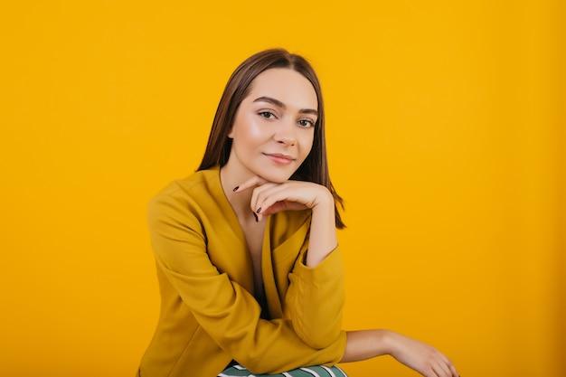 Modello femminile in posa giacca gialla alla moda. foto dell'interno della donna castana soddisfatta con la posa dei capelli scuri