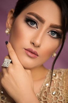 Female model in wedding bridal makeup demonstrating jewelry