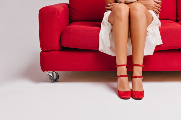 Female model in white dress and red shoes sitting on couch. graceful tanned girl posing on sofa.