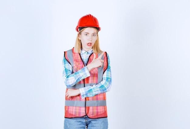 빨간 헬멧과 안전 조끼가있는 여성 모델이 흰 벽 앞에 손 기호를 만드는