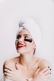 Modello femminile con labbra rosse guarda verso l'alto con entusiasmo. ragazza in asciugamano dopo la doccia in posa sul muro bianco.